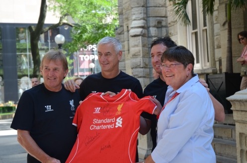 Chicago Architecture Foundation representative receives a signed team jersey from Kenny Dalglish, Ian Rush and Robbie Fowler in front of the Water Tower in Chicago, Summer 2014.